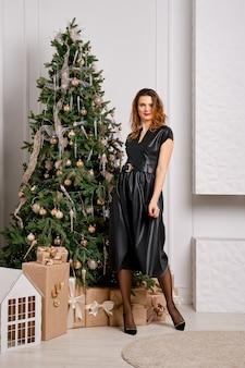 아름 다운 여자 가죽 드레스를 입고 크리스마스 트리 근처 dansing 미소와 행복 느낌