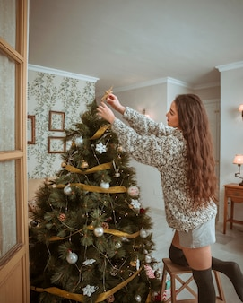 Beautiful woman decorating Christmas tree in living room