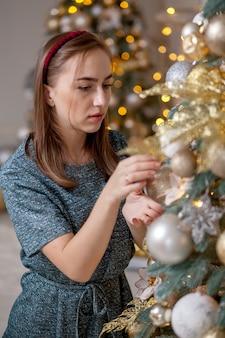 Красивая женщина украшает елку