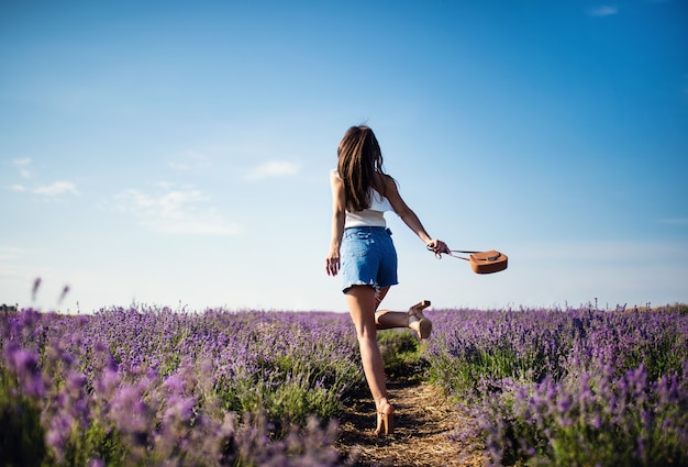 Beautiful woman denim shorts in the lavender field on sunset. fantastic summer mood.