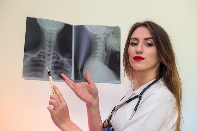 병원에서 엑스레이를 가리키는 아름다운 여성 의사. 진단을 내리는 의사