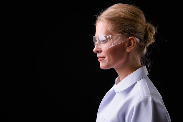 Beautiful woman doctor with blond hair as scientist wearing protective glasses against black wall