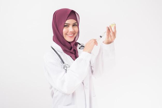 ヒジャーブと美しい女性医師が白い背景の上のワクチンを保持しています。