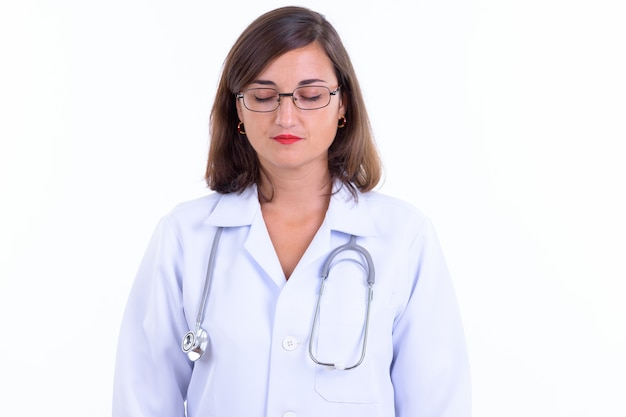 Beautiful woman doctor with short hair wearing eyeglasses isolated against white wall