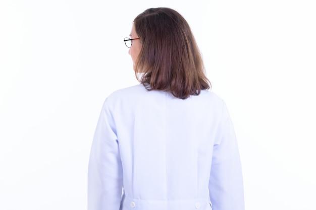 흰 벽에 고립 된 안경을 쓰고 짧은 머리를 가진 아름 다운 여자 의사