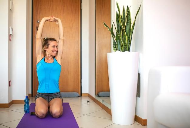 Красивая женщина делает гимнастику упражнения в гостиной комнате дома.