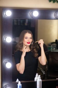 Красивая женщина делает макияж и смотрит в зеркало