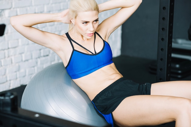 Beautiful woman doing abdominal crunches on fitball