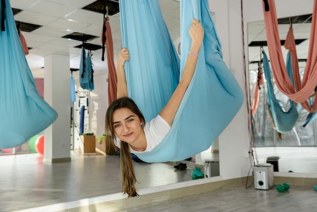 Красивая женщина делает упражнения воздушной йоги в классе