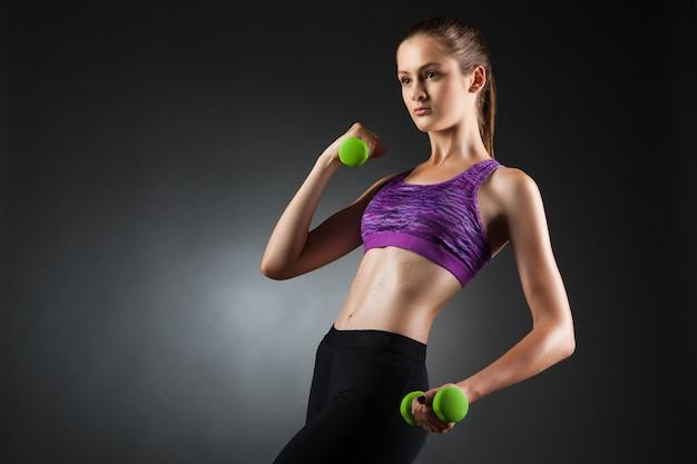 緑のダンベルで上腕二頭筋のエクササイズをしている美しい女性。スタジオポートレート黒ビネット背景。