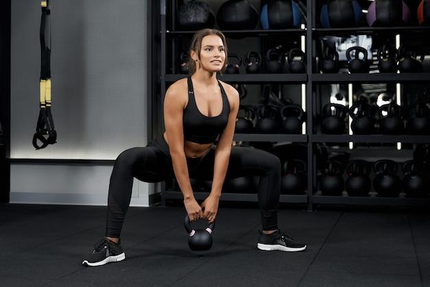 Красивая женщина делает упражнения с гирями