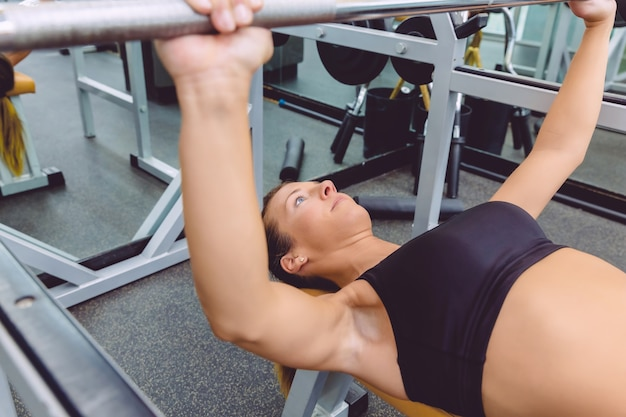 Beautiful woman doing exercises with barbell on a bench press training in a fitness center