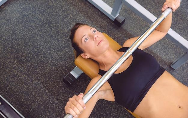 フィットネスセンターでベンチプレストレーニングでバーベルでエクササイズをしている美しい女性
