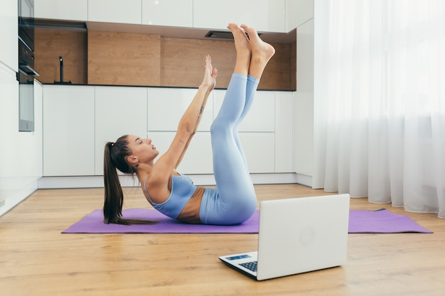 Красивая женщина занимается фитнесом дома онлайн с ноутбуком