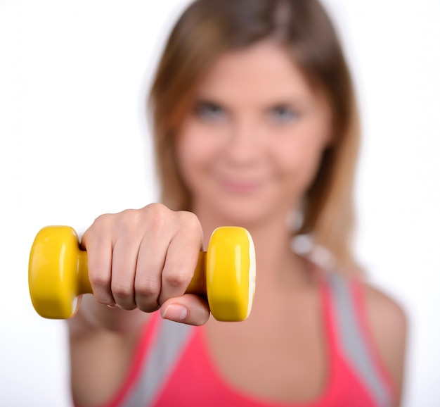 Beautiful woman doing fitness exercise with dumbbells.