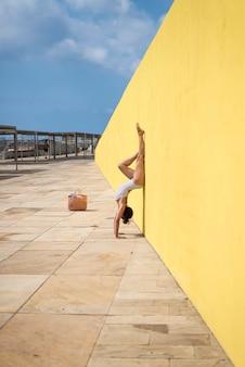 Beautiful woman doing a handstand wearing swimwear