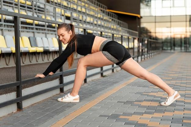 Bella donna che fa il suo allenamento all'aperto