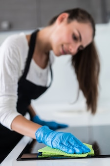 Beautiful woman doing the housework while cleaning in the kitchen