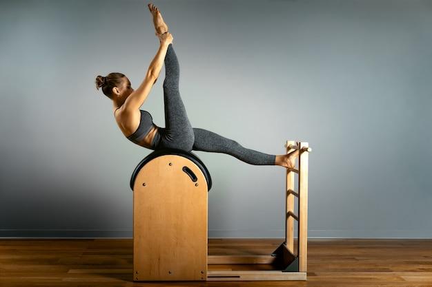 Beautiful woman doing pilates exercise training on barrels barrel reformer correct posture healthy locomotor system
