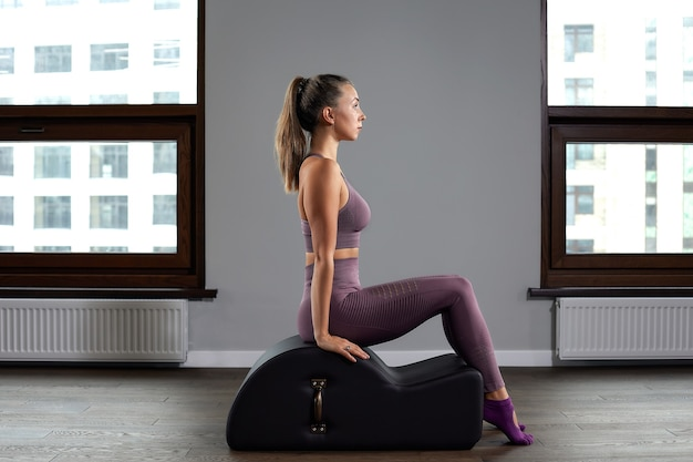 Beautiful woman doing pilates exercise, training on barrels. fitness concept, special fitness equipment, healthy lifestyle, plastic. copy space, sport banner for advertising.