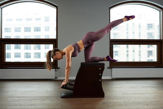 필라테스 운동, 배럴 훈련을 하는 아름다운 여성. 피트니스 개념, 특수 피트니스 장비, 건강한 생활 방식, 플라스틱. 공간, 광고용 스포츠 배너를 복사합니다.