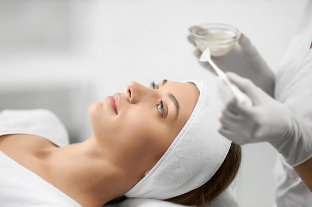 Beautiful woman doing procedure for face in beautician