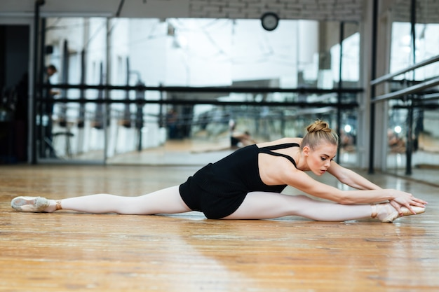Красивая женщина делает упражнения на растяжку на полу в балетном классе