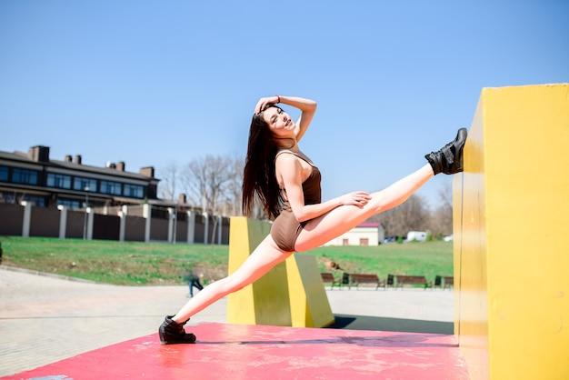 Красивая женщина делает растяжку на спортивной площадке Premium Фотографии