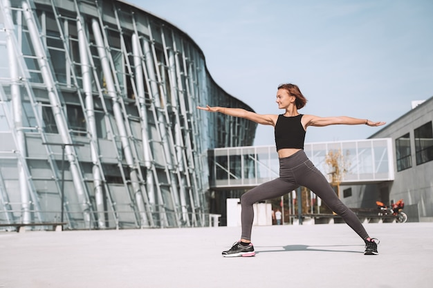 Beautiful woman doing stretching yoga exercises outside in the city
