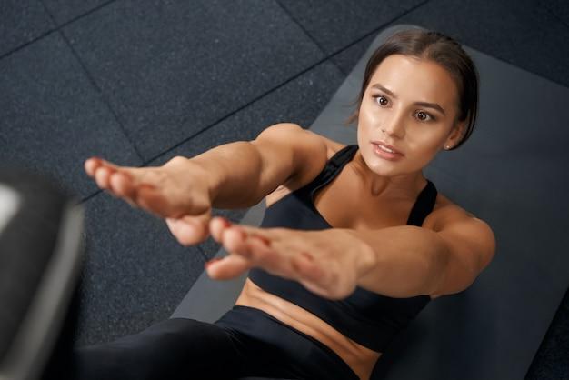 Красивая женщина делает тренировку на коврике