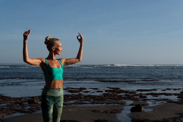 Beautiful woman doing yoga on the beach