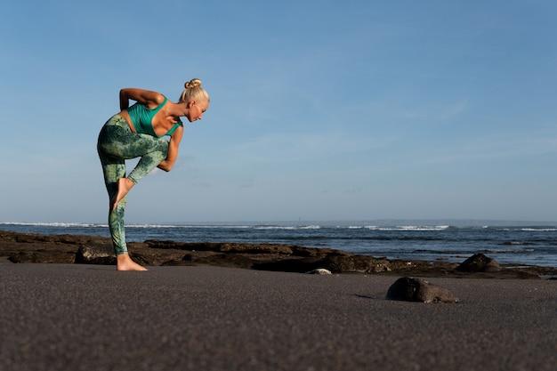 ビーチでヨガをしている美しい女性
