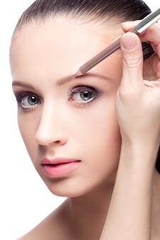 눈썹 연필을 사용하여 눈썹 모양을 그리는 아름 다운 여자. 모델에 메이크업을 적용하는 메이크업 아티스트