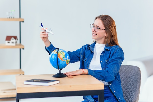 Beautiful woman dreaming about vacation. girl holds in hand a model of airplane and flies around small globe.