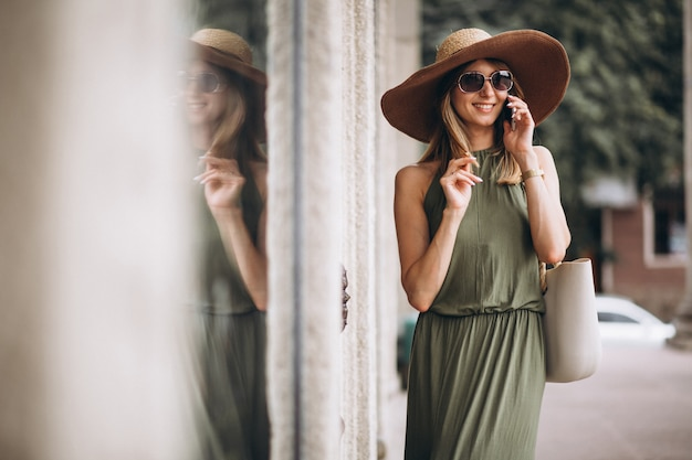 Beautiful woman in dress and hat talking on the phone