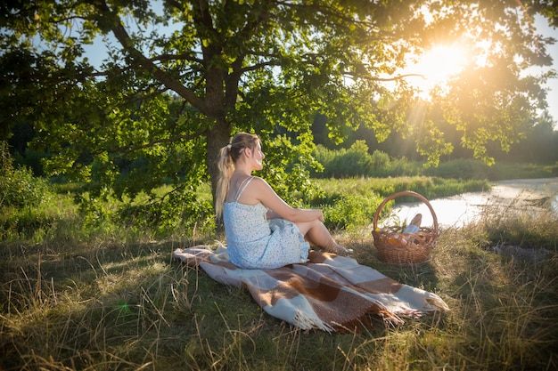 Beautiful woman in dress relaxing on blanket under tree and looking at sunset