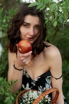 Beautiful woman in a dress with an apple in her hands, sits in the garden.