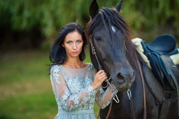 Beautiful woman in dress with black horse in nature