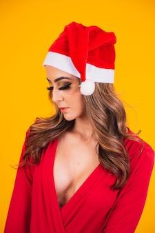 Beautiful woman dressed as mama noel wearing christmas hat