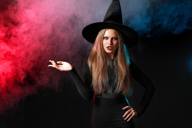 어둠에 할로윈 마녀로 분 장 한 아름 다운 여자