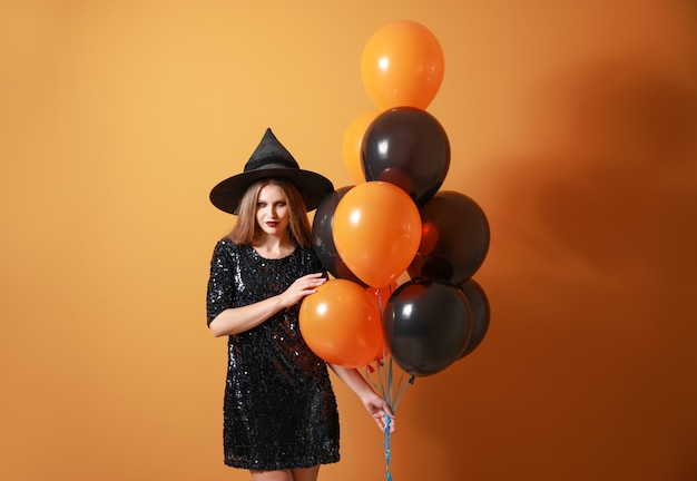 Beautiful woman dressed as witch for halloween on color