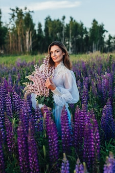 Beautiful woman dressed in a dress in flowers lupines at sunset
