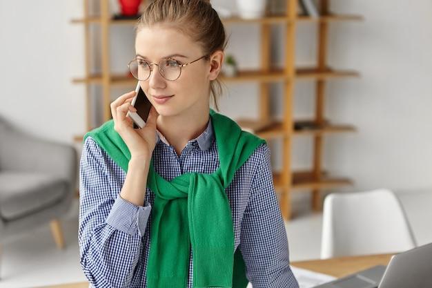 電話でオフィスで正式に服を着た美しい女性