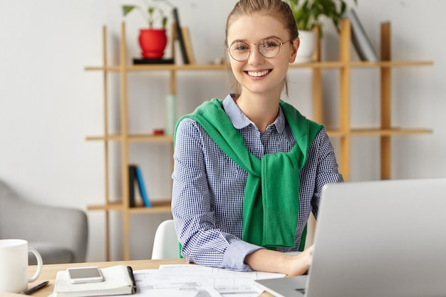 Beautiful woman dressed formally in office with laptop