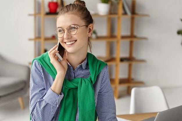 Beautiful woman dressed formally in office with phone