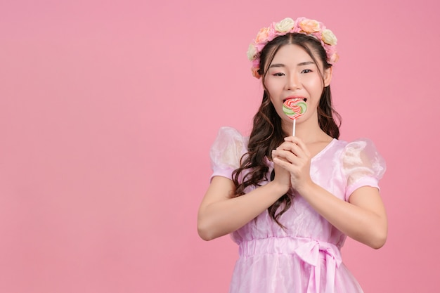 A beautiful woman dressed in a pink princess is playing with her sweet candy on a pink .