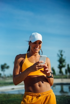 Beautiful woman dressed in sports using mobile cell phone.
