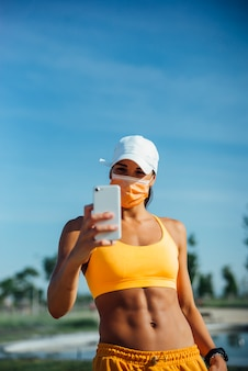 Beautiful woman dressed in sports with mask using mobile cell phone.