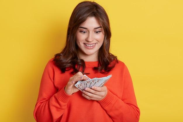 Красивая женщина одевает оранжевый свитер и держит веер с деньгами, изолированным над желтой стеной, выглядит изумленной, привлекательная женщина с большими глазами готова пойти по магазинам.