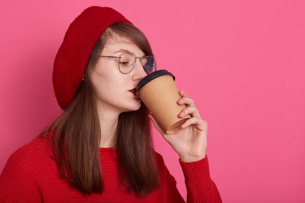 美しい女性は赤いシャツ、眼鏡、ベレー帽、プラスチック製のマグカップでコーヒーのカップを保持している魅力的な女の子のプロフィールを飲んでホットbaverage